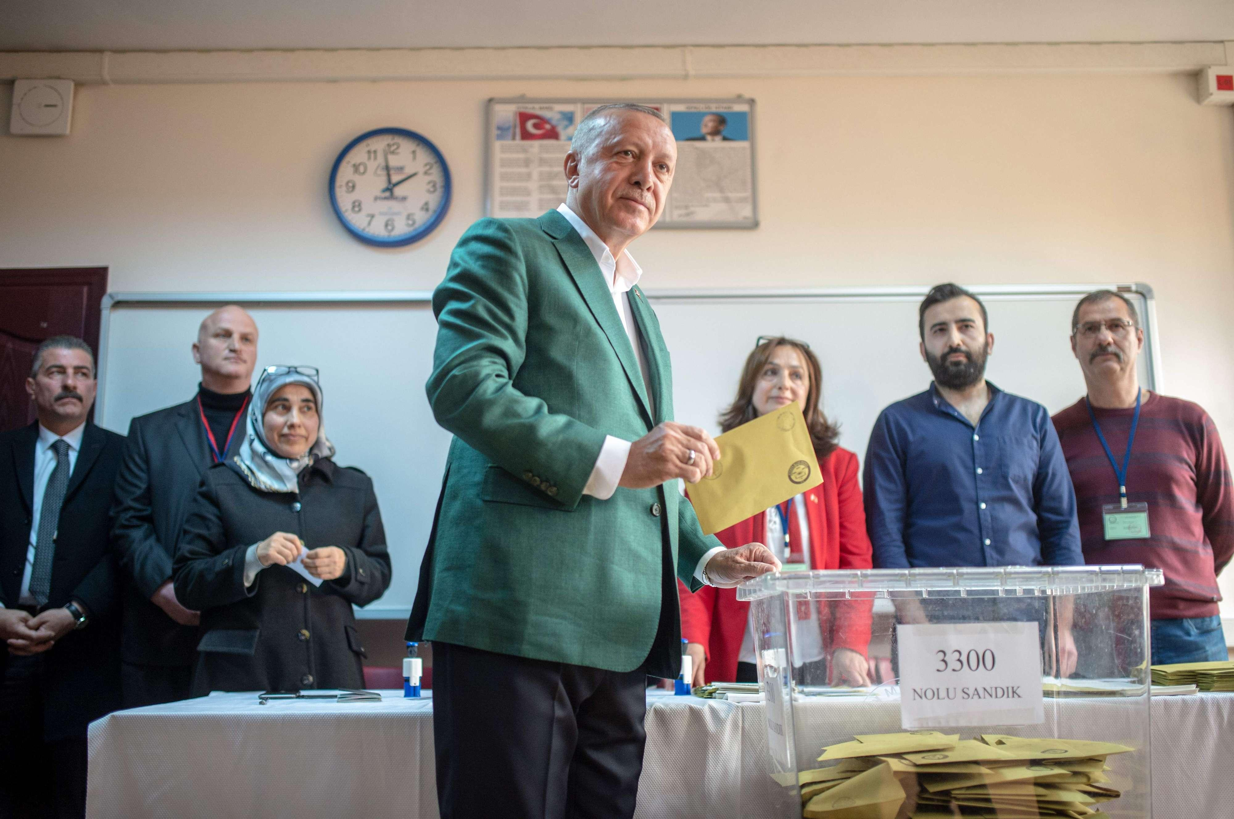 Turkish President Tayyip Erdogan (C) stands prior to cast his ballot at a polling station during the municipal elections in Istanbul.