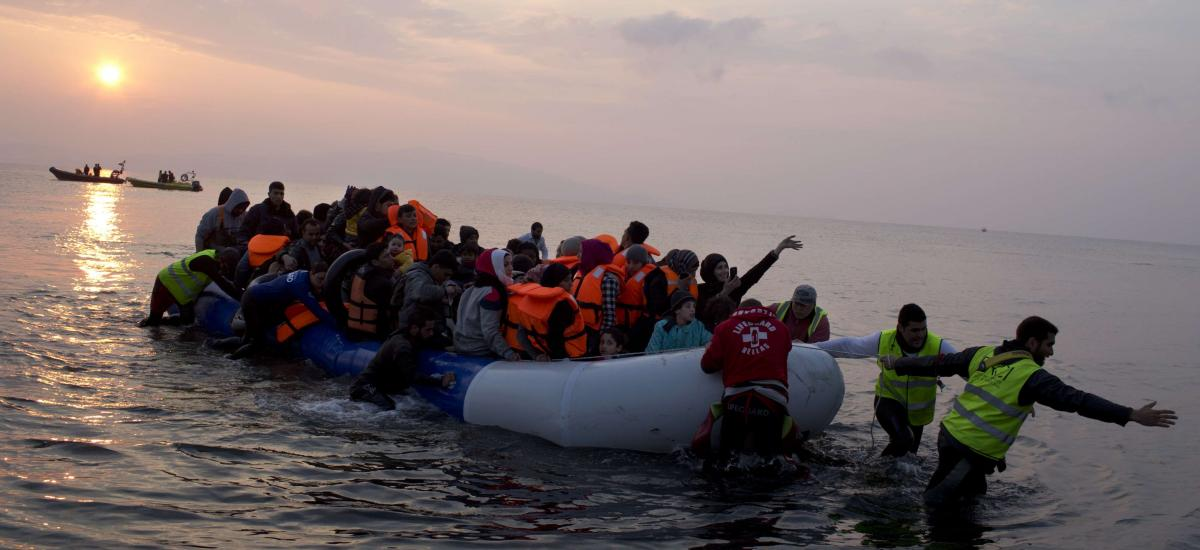 Volunteers help migrants and refugees on a dingy as they arrive at the shore of the northeastern Greek island of Lesbos, after crossing the Aegean sea from Turkey in 2016.