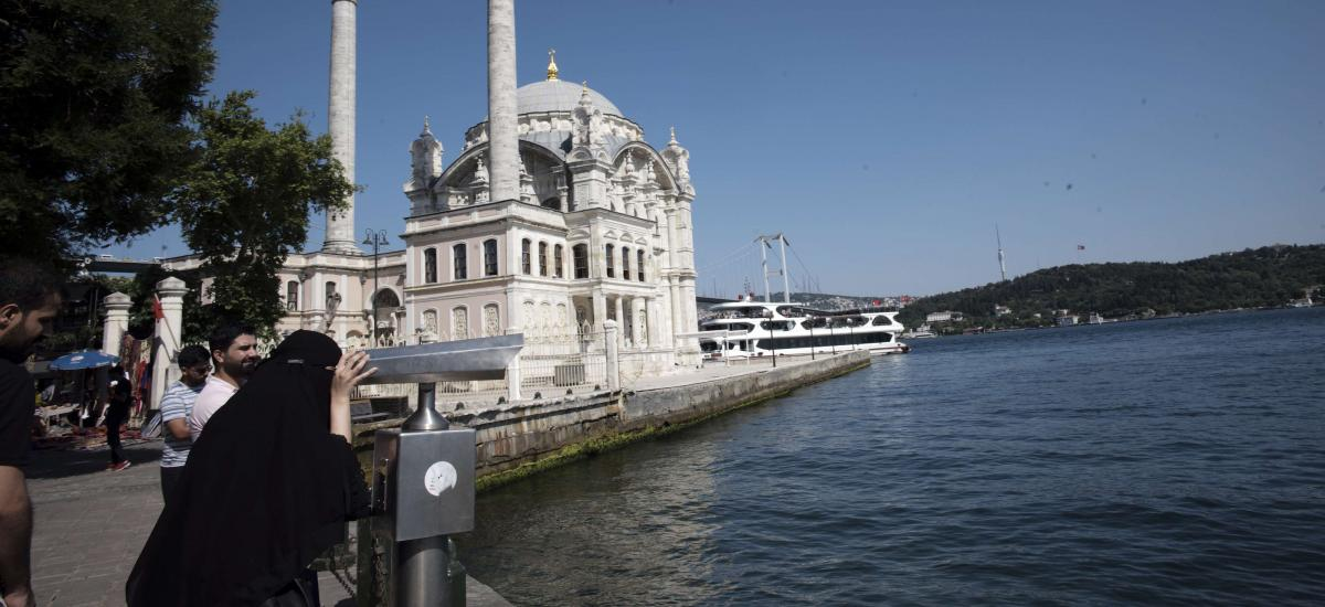 Arab tourists use binoculars to look around with Mecidiye Mosque and Bosporus Bridge in the background, in Istanbul, Monday, June 24, 2019.
