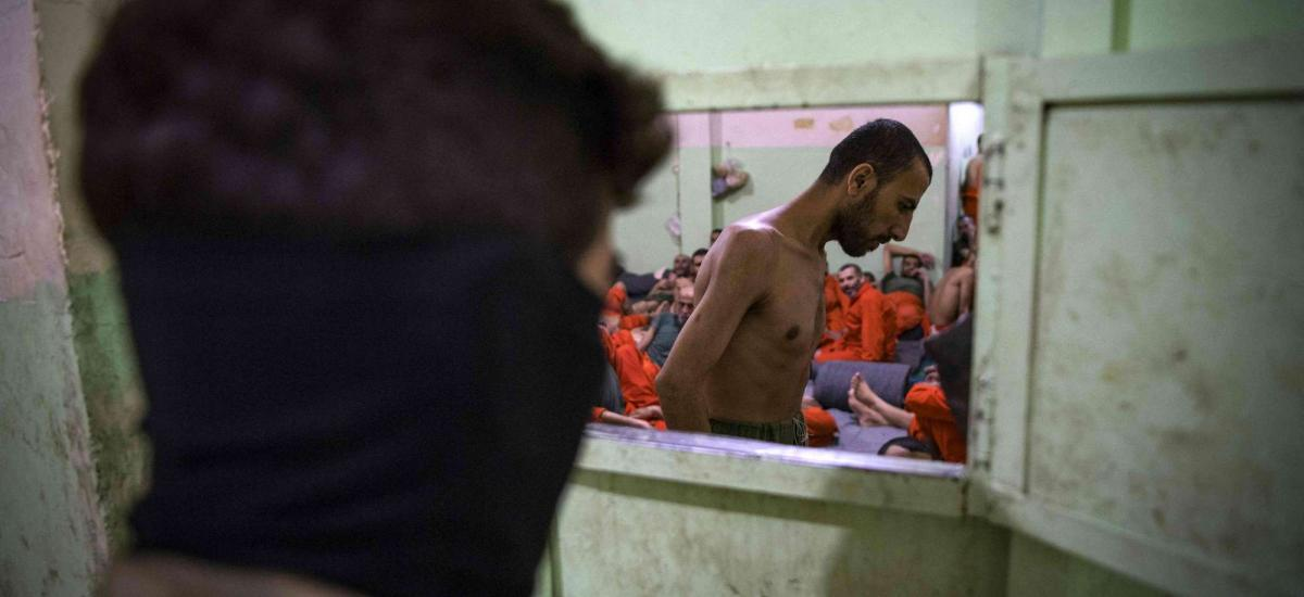 member of the Syrian Democratic Forces (SDF) ISIS stands near prisoners in a prison in northeast Syria in the city of Hasakeh on October 26, 2019