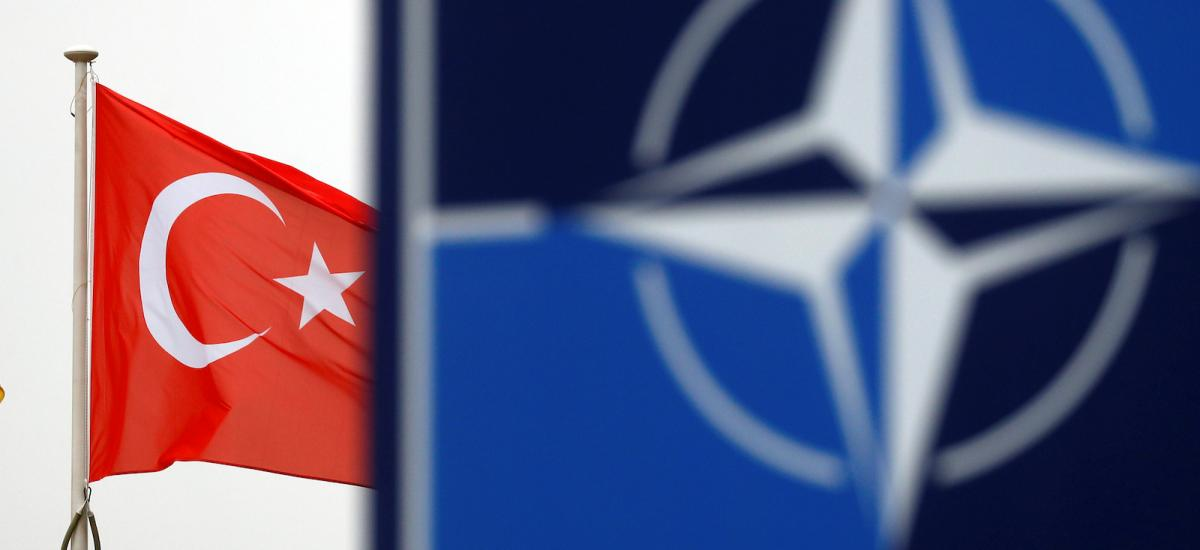 A Turkish flag flies next to NATO logo at the Alliance headquarters in Brussels, Belgium, November 26, 2019.