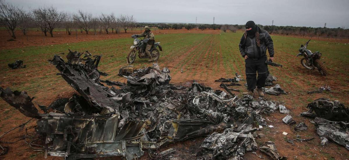 Syrian rebels look at the wreckage of a military helicopter belonging to Syrian government forces after it was shot down in the rebel-held Idlib province.