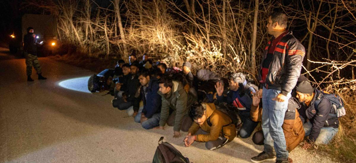 Greek Army soldiers detain a group of migrants in the region of Evros, Greece