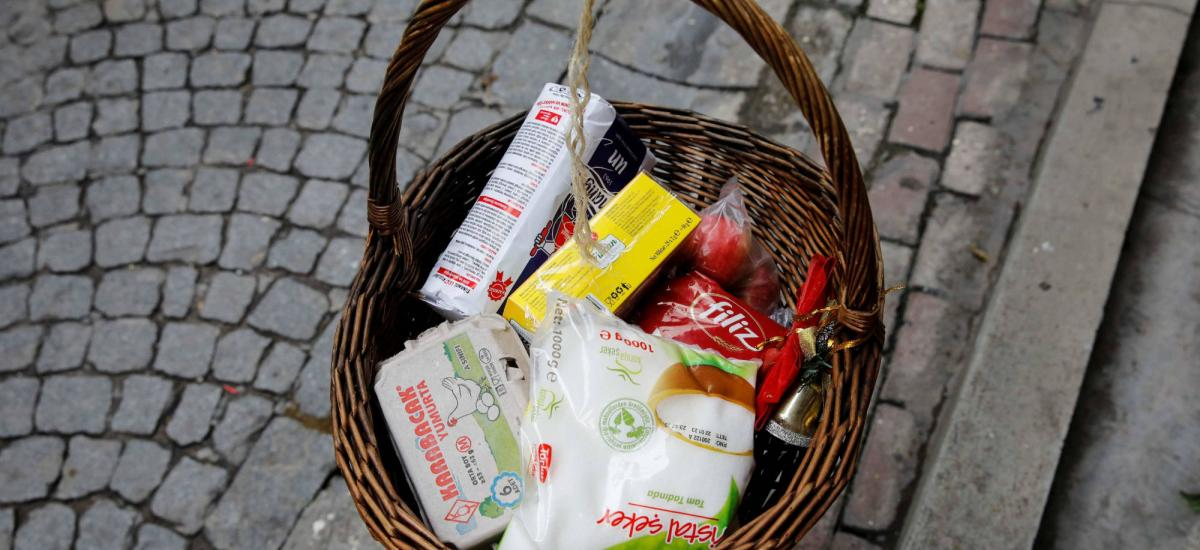 "A basket with free food is seen as it lowered from the window of Jeffrey Tucker as a sign of social solidarity with poor and homeless people in need amid the coronavirus disease (COVID-19) outbreak in Istanbul, Turkey April 3, 2020. Cardboard reads, ""Those who have the means, add. Those who need, take"" REUTERS/Umit Bektas"