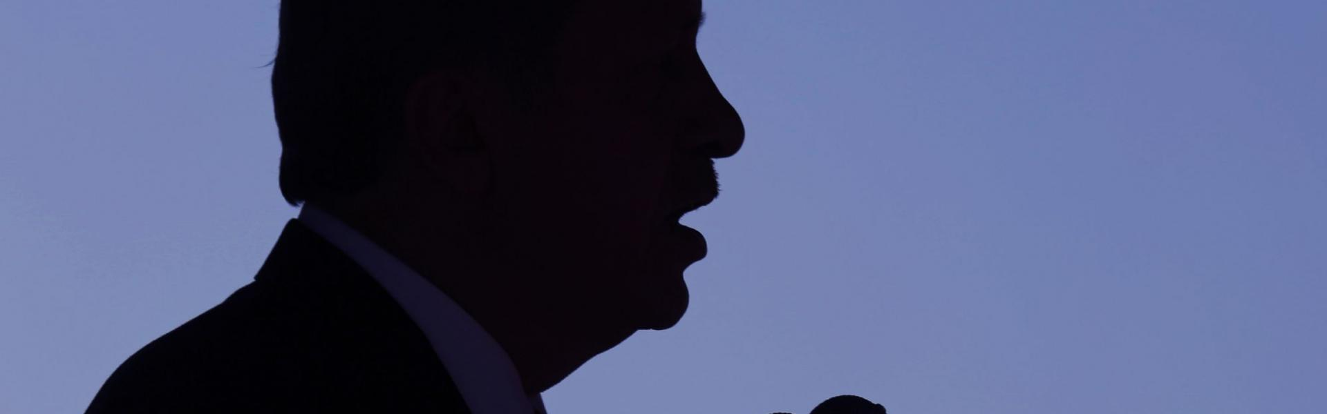 Turkish President Recep Tayyip Erdogan, in silhouette, speaks during during a military parade in 20015.