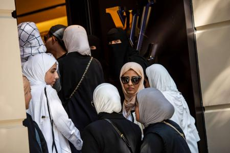 Veiled women, many from Saudi Arabia and Asia, queue outside a luxury brand Louis Vuitton store in Istanbul on August 13, 2018. Akgul/AFP
