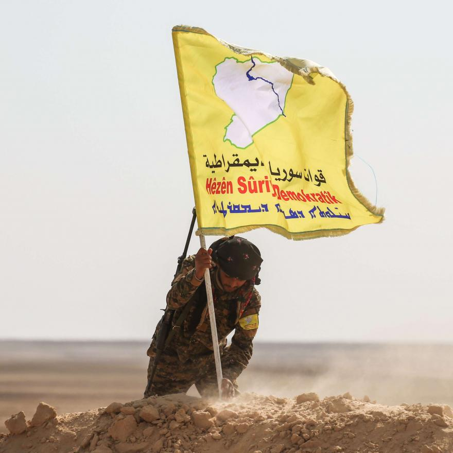 This file photo taken on February 8, 2017 shows a member of the Syrian Democratic Forces (SDF), made up of US-backed Kurdish and Arab fighters, raising a flag of the SDF near the village of Bir Fawaz, 20 km north of Raqa. AFP / DELIL SOULEIMAN