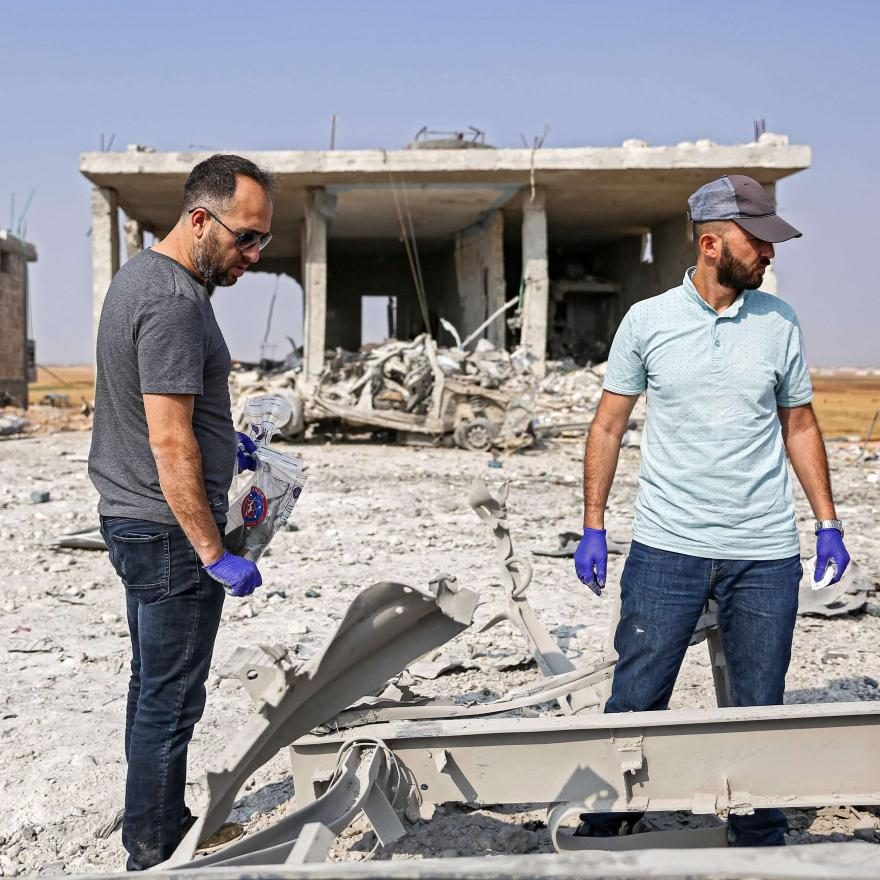 Turkish forensic experts collect samples as they inspect the scene of a rigged-car explosion in the Syrian town of al-Rai, held by pro-Turkish Syrian fighters, in the north of Aleppo province along the border with Turkey, on September 16, 2019. (Photo by Nazeer Al-khatib / AFP