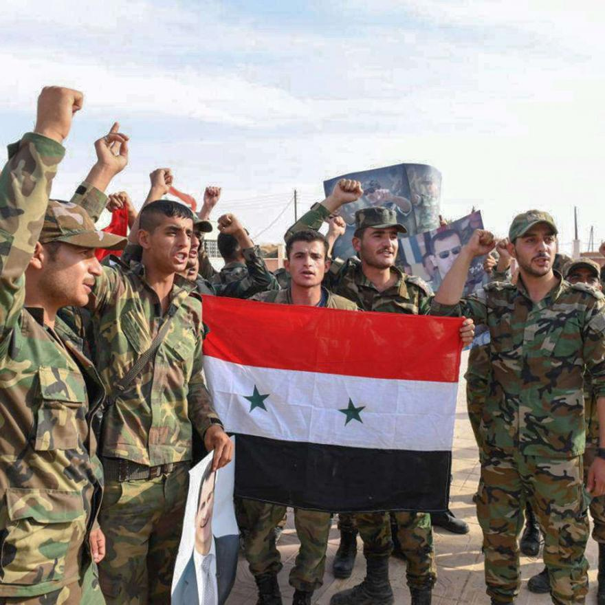 A handout picture released by the official Syrian Arab News Agency (SANA) on October 15, 2019 shows a Syrian army troops posing with a national flag after reportedly completing their deployment in the Syrian northern city of Manbij.