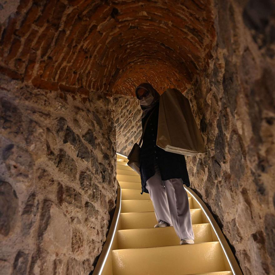 A woman walks upstairs after the restoration of the Galata Tower on October 16, 2020 in Istanbul. - The Galata Tower -- an emblematic 14th century monument of Istanbul -- has become the latest victim of such controversy. The demolition of one of its walls with a jackhammer as part of a restoration work was narrowly avoided last August after a video leaked on social media, which sparked strong criticism from the largest city's residents. (Photo by Ozan KOSE / AFP)